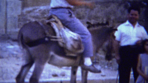 1954: Happy man rides donkey urban old Italian urban town Stock Video Footage