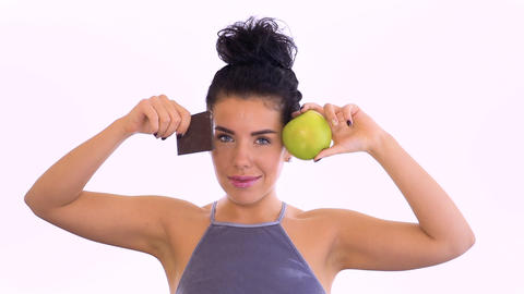 Beautiful brunette with green apple and chocolate is posing at white background Footage