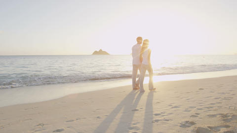 Beach couple walking happy by sunrise on vacation Footage