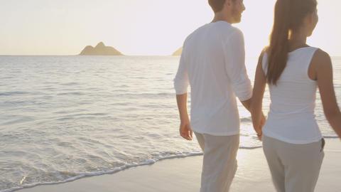 Couple holding hands on beach sunset on honeymoon Live Action