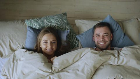Top view of smiling couple having fun in bed hiding under blanket and looking Footage