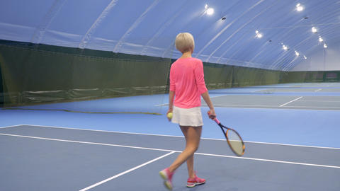 Young woman plays tennis at the indoors court Footage