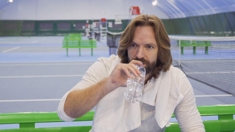Tennis player with towel on shoulders relax after the game and drinks water Footage