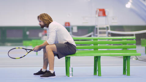 Handsome adult man with racquet sit on bench at tennis court Footage