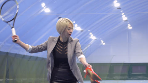 Young businesswoman with shoes in hand professionally play tennis Footage