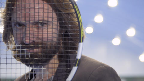 Portrait of handsome man looks through tennis racquet and smiles Footage