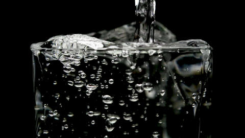 Water pouring into clear glass black background Image