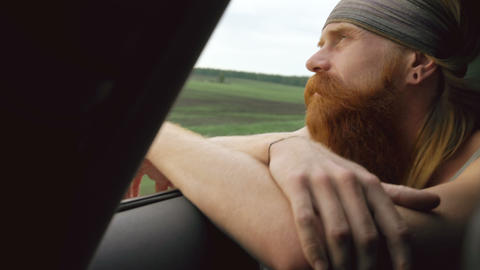 Happy young tourist man watching in car window relaxed while traveling Footage