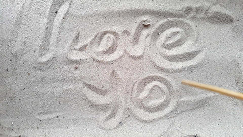 writes the words i love you, on the sand of the beach with a seashell and a 영상물
