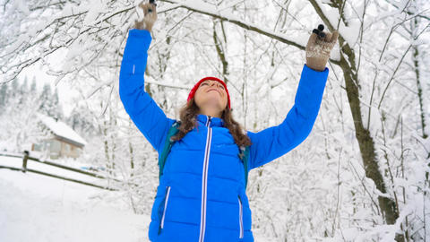 Woman is having fun - she is shaking the branches of a tree and snow is falling Footage