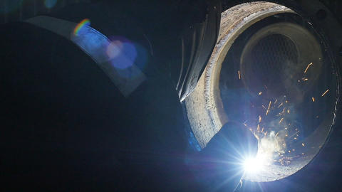 The worker with the welding mask inside the factory. The welding process of a Footage