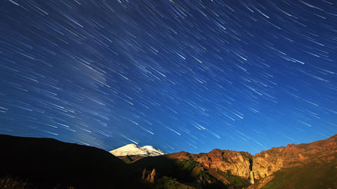 Stars draw fading lines and clouds over Mount Elbrus. Night landscape. Russia Footage