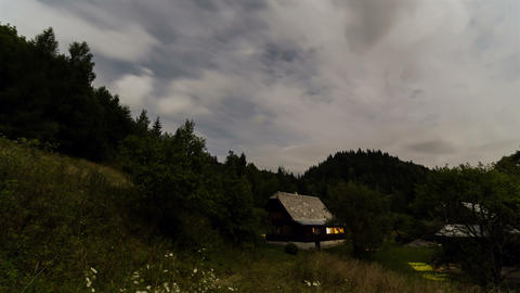 Clouds moving over cottage at night time lapse. Romantic evening in wood cabin Footage