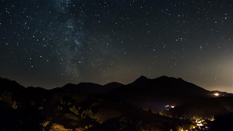 Starry night on countryside time lapse. Stars moving in sky with milky way Footage