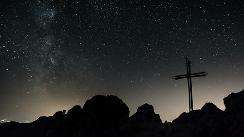 Time lapse of stars moving in night sky over cross symbol of Jesus Christ dolly Footage