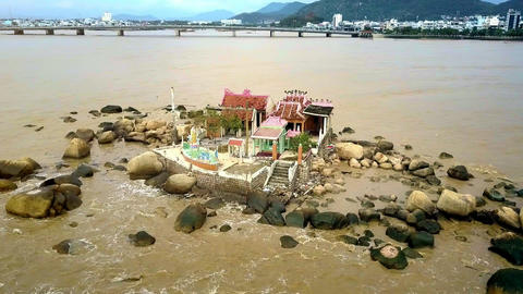 Temple among Boulders at Sea against City River Bridge Footage