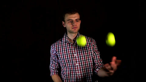 male hipster juggles on a black background, human hobby Live Action