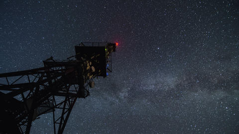 Communication tower in starry night time lapse. Moving stars sky with milky way Footage