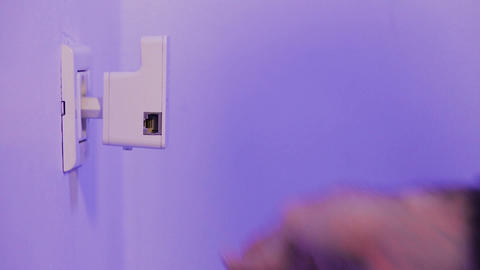 Man insert WiFi repeater into electrical socket on the wall. The device help to Footage