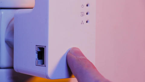 Man press with his finger on WPS button on WiFi repeater which is in electrical Footage