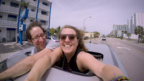 Couple standing through a sunroof of a car smiling at camera while being driven ビデオ