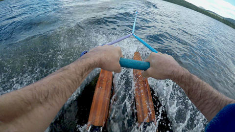 POV of a man successfully getting up on his vintage wooden water skis in a Footage