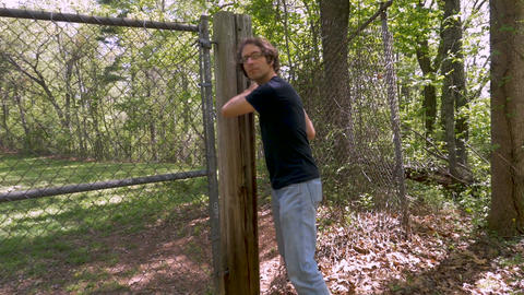 Wide of a man breaking into a chained off area and creeping into the woods in Footage