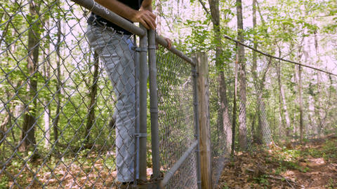 Man in his 30s or 40s climbing over a chain link fence trespassing on private Live Action