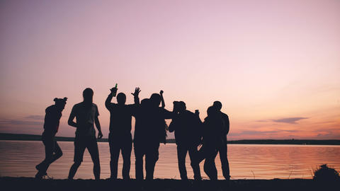 Silhouette of Group young dancing people have a party at beach on sunset Footage