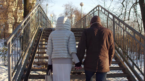 Couple walking holding hands on a small bridge full of love locks. 4K steadicam Footage
