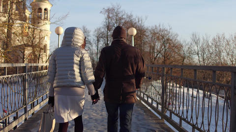 Couple walking holding hands on a small bridge full of... Stock Video Footage