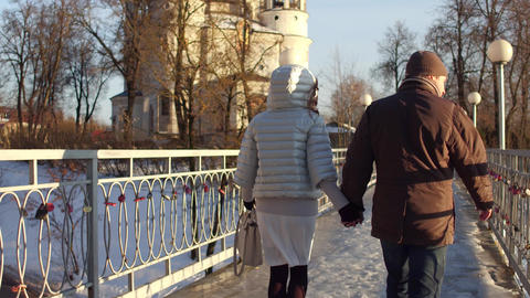 Man and woman walking holding hands on a bridge full of love locks Footage