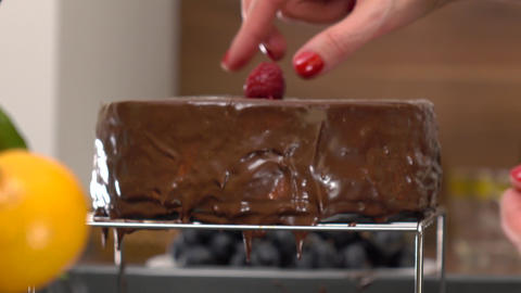 Beautiful woman hands placing raspberries onto freshly cooked chocolate cake. 4K Footage