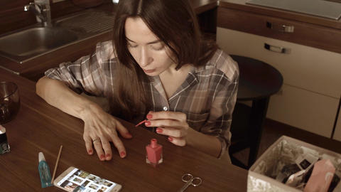 Beautiful brunette woman giving herself manicure at home Footage