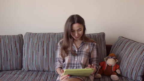 Beautiful brunette woman using her tablet PC at home. 4K close up steadicam Footage