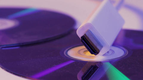 Closeup of white HDMI cable with it's reflection on blank disc Footage