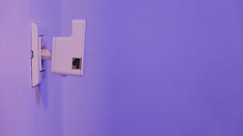 WiFi repeater in electrical socket on the wall. Device that help to extend Live Action