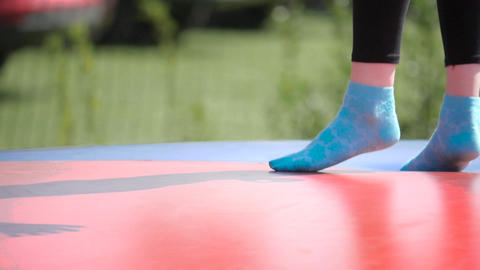 Close up of children's feet in bright patterned socks on trampoline Live Action