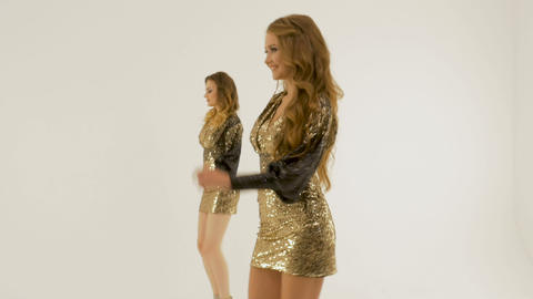 Two beautiful girls in shiny dresses dancing and singing in the studio on a Footage