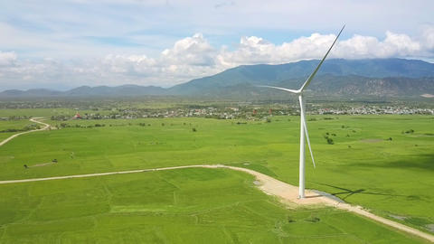 Fresh Meadow with Wind Turbine and Mountain Upper View Stock Video Footage