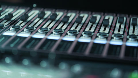 audio mixer in a studio, the automatic knobs moving up on console. Close-up DOF Footage