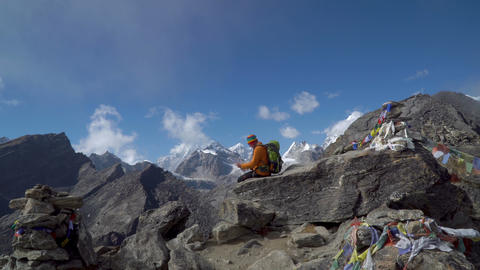 A guy with a map sits on a rock Footage
