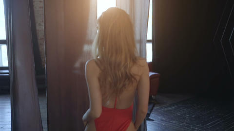 Sexy girl in red swimsuit goes towards the window Footage