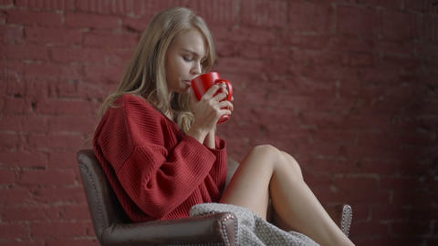 Young girl in sweater with red cup of coffee in hands sitting in armchair and Footage