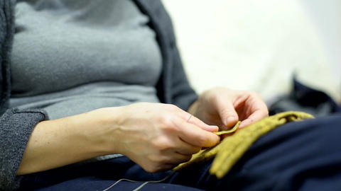 A woman sews a dress for a doll with a needle thread Footage