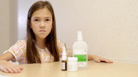the girl takes vitamins and drinks with water. Little girl sitting at table Footage