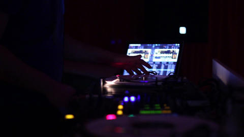 Dj behind the deck. DJ's hands moving from one tool to another Live Action