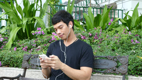 Guy sitting on a bench at Benjasiri Park listening to music on his phone Footage