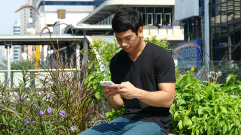 Guy Sitting On A Bench Outside Emporium Shopping Mall And Looks At His Phone stock footage