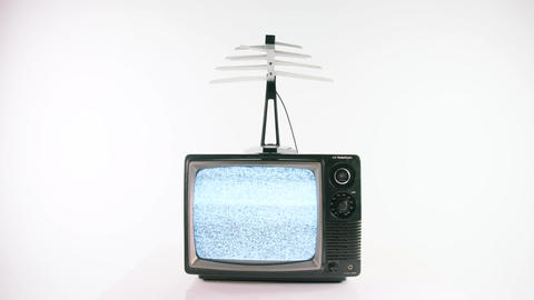 Vintage television with antenna turning on and playing static Footage